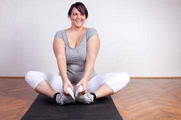 Overweight woman stretching on the floor