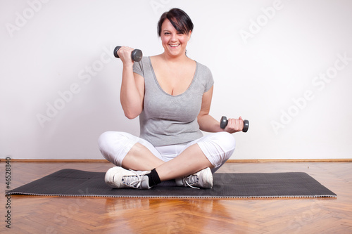 Happy overweight woman lifting weights