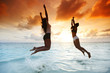 Two happy women jumping on beach