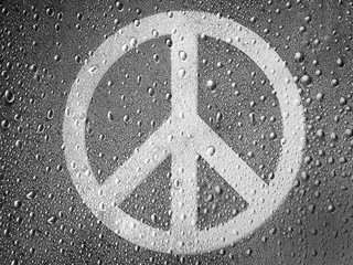 Peace symbol painted on metal surface covered with rain drops