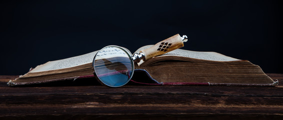 magnifing glass and old book