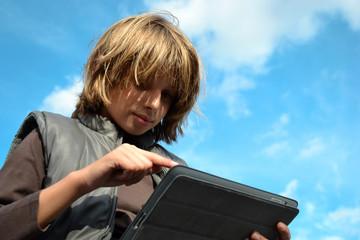Enfant blond pointant sur tablette numérique