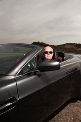 Senior good looking happy retired man driving his sports car