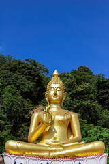 The big golden Buddha statue on hill with blue sky background