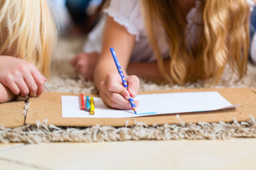 Family at home, the children coloring on floor