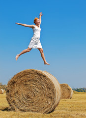 Young woman having fun on the field with big hay bale rolls