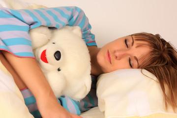 Mujer rubia durmiendo con oso de peluche