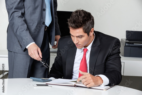 Two Businessmen Calculating Finances