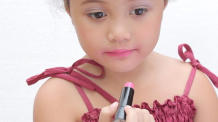 Young girl applying a lipstick