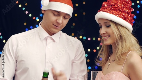 Handsome man pouring champagne with girlfriend