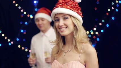 Happy  man in santa claus hat bring drink to woman