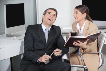 Geschäftsmann und Sekretärin lachen