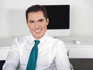 Lächelnder Geschäftsmann am Schreibtisch