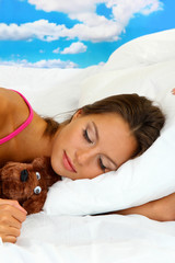young beautiful woman with fluffy bear sleeping in bed