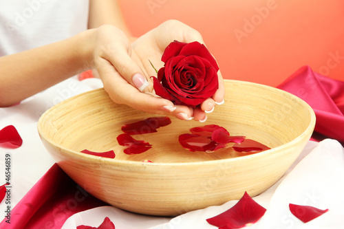 woman hands with wooden bowl of water with petals,