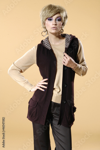The fashionable young woman standing on beige background