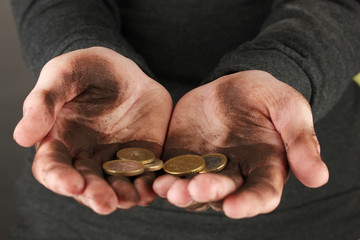 homeless man holding a coins, close-up