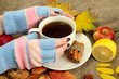 hands holding cup of hot drink and autumn leaves,