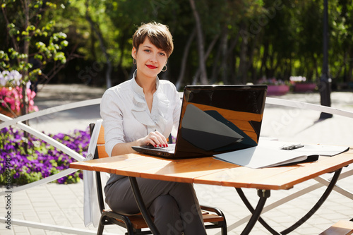 Young businesswoman with laptop at a sidewalk cafe