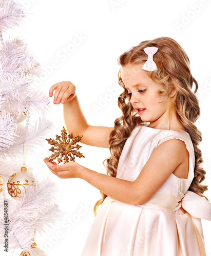 Child holding snowflake to decorate Christmas tree .