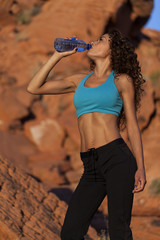 Fit woman on hike drinks water.