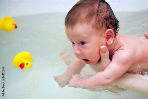Baby newborn learning to swim and playing sports