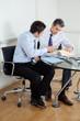 Businessmen Discussing Paperwork In Office