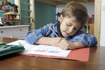 Schulkind sitzt über seinen Hausaufgaben
