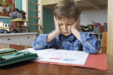 Kind macht wiederwillig Hausaufgaben