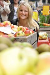 Junge Frau kauft Äpfel auf Markt