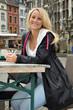 Junge Frau sitzt in Straßencafé