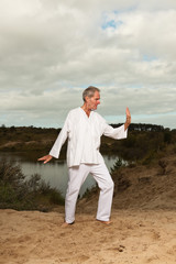 Senior spiritual man dressed in white. Exercising outdoors.