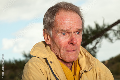Senior man with yellow coat. Having cold. Sad looking.