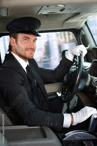 Young chauffeur in limousine smiling