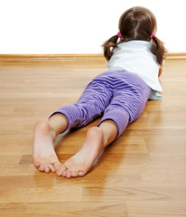 barefoot - a little girl resting on a wooden floor
