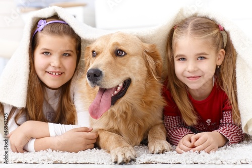 Little sisters having fun with pet dog