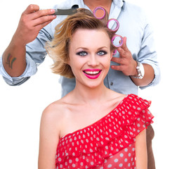 Hairdresser making a hairstyle from blond woman, isolated