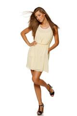 Full length of young elegant female in light yellow summer dress