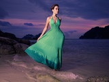Lady in green dress on seashore