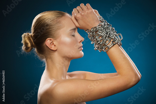 Closeup of beautiful female model with chained hands