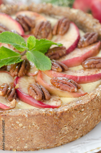cheesecake with apples and caramelized pecans closeup selective