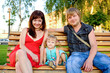 Happy beautiful family relaxing on park bench