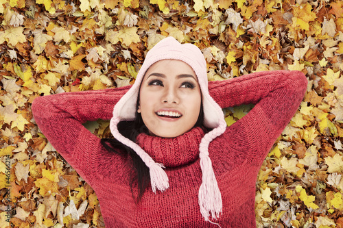 Happy woman laying on Autumn leaves