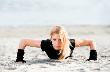 Beautiful fit woman doing push ups on the beach