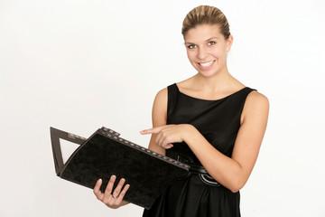 Glückliche Geschäftsfrau zeigt auf ihre Mappe