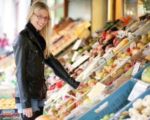 Junge Frau kauft an einem Marktstand ein