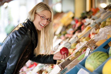 Glücklche Frau kauft Gemüse