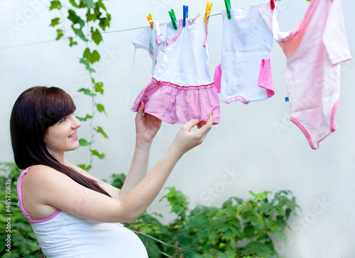 portrait of pretty young woman expecting a baby,outdoors