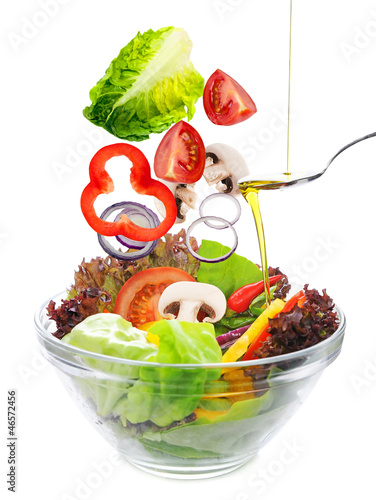 salad of fresh vegetables falling in a bowl