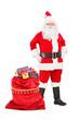 Santa Claus posing next to a bag full of gifts